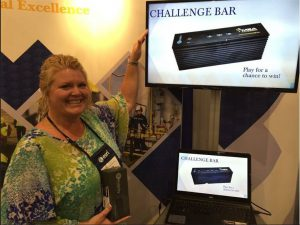 Proud winner of trade show trivia game points to prize she won